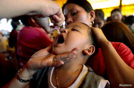 FILE PHOTO: A child receives free polio vaccine during a government-led mass vaccination program in Quezon City, Metro Manila,…