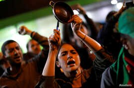 Demonstrators bang pots as they join a call for what they say is a simultaneous cacerolazos (pot-banging protests) throughout…