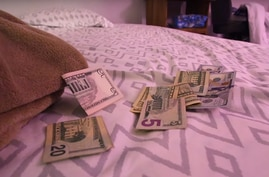 FILE - Money is seen on a bed used for prostitution during a 2017 multi-agency initiative to recover people who were  trafficked in this US Federal Bureau of Investigation photo.