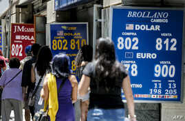 People walk past a bureau de exchange were currency exchange is displayed in Santiago, Chile, Dec. 2, 2019.