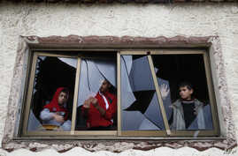 Palestinian boys pull shards of glass from a broken window at their home near the site of Israeli overnight attacks in Gaza City, Dec. 8, 2019.