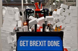 Britain's Prime Minister Boris Johnson drives a JCB through a symbolic wall with the Conservative Party slogan 'Get Brexit Done' in the digger bucket, during an election campaign event at the JCB manufacturing facility in Uttoxeter, England.
