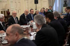 Greek foreign Minister Nikos Dendias, facing third left, takes part in a meeting with political party representatives on developments for the maritime boundary deal between Turkey and Libya in Athens, Dec. 10, 2019.
