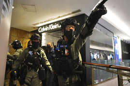Riot police gesture as they gather at a shopping mall during a demonstration in Hong Kong, Dec. 26, 2019.