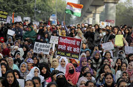 Indian students of the Jamia Millia Islamia University and locals participate in a protest against a new citizenship law, in New Delhi, India, Dec. 21, 2019.