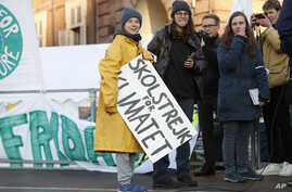 """Swedish environmental activist Greta Thunberg holds a sign with writing reading in Swedish """"School strike for the climate"""" as…"""