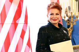 FILE - Georgette Mosbacher stands next to an American flag after receiving her credentials as United States ambassador to Poland in Warsaw, Sept. 6, 2018.