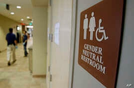 FILE - A sign marks the entrance to a gender-neutral restroom at the University of Vermont in Burlington, Vermont, Aug. 23, 2007.