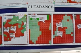 Maps indicating the progress of UXO technical surveys and clearance operations are displayed at the MAG office in Phonsavan, Nov. 1, 2019. (Zsombor Peter/VOA)