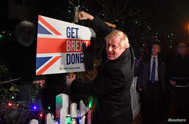 """FILE - Britain's Prime Minister and Conservative party leader Boris Johnson poses with a sledgehammer, after hammering a """"Get Brexit Done"""" sign into the yard of a supporter, in South Benfleet, Britain, Dec. 11, 2019."""