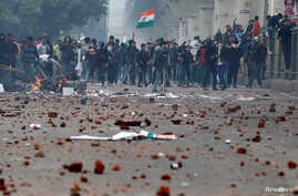 Demonstrators throw stones towards police during a protest against a new citizenship law, in the Seelampur area of Delhi, India, Dec. 17, 2019.