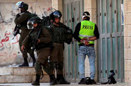 FILE - Israeli soldiers detain a local Palestinian cameraman during clashes with Palestinians in the village of Tuqu, near Bethlehem, in the Israeli-occupied West Bank, Jan. 25, 2019.