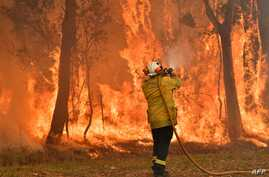 A firefighter conducts back-burning measures to secure residential areas from encroaching bushfires in the Central Coast, some 90-110 kilometers north of Sydney, Australia.