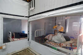 FILE - Moise Vaghemi, an Ebola survivor who works as a nurse, tends to a suspected Ebola sufferer inside the Biosecure Emergency Care Unit at an Ebola treatment center in Katwa, DRC, Oct. 3, 2019.