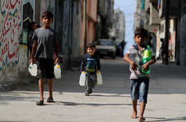Palestinian boys carry bottles of water in Al-Shati refugee camp in Gaza City, Oct. 23, 2019.