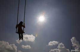 FILE - A girl plays on a swing during the Hindu festival of Dasain in Kathmandu, Nepal, Sept. 29, 2011.
