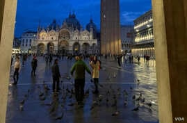 FILE - Tourists are seen in Venice's iconic St. Mark's square after November floodwaters receded. (Sabina Castelfranco/VOA)