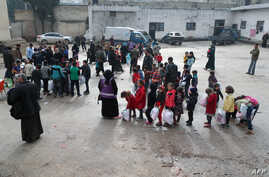 Children of Syrian families displaced from the Maaret Al-Numan region gather in the yard of a former jail turned into a…