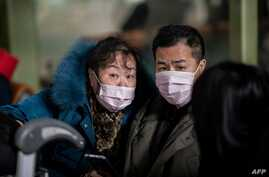 People travelling for the Lunar New Year wear protective masks as they head to the departure area at the Beijing Capital…