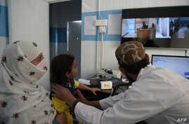 This photograph taken on October 20, 2017, a Pakistani paramedic checks a child at a telemedicine online treatment centre run…
