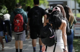 In this Tuesday, Oct. 23, 2018 photo, students walk on the campus of Miami Dade College, in Miami. (AP Photo/Lynne Sladky)