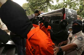 Police anti-terror unit Special Detachment 88 escort suspected militants before a press conference in Jakarta, Indonesia,…