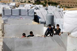 FILE - Displaced Syrian children climb a concrete wall at a refugee camp in the eastern Lebanese border town of Arsal, Lebanon, Aug. 5, 2019.