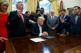 FILE - Religious leaders pray with President Donald Trump after he signed a proclamation for a national day of prayer to occur on Sunday, Sept. 3, 2017, in the Oval Office of the White House in Washington.