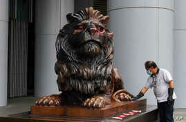A worker cleans the iconic lion statue in front of the international HSBC Bank branch that was painted with red paint in Hong…
