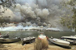 Boats are pulled ashore as smoke and wildfires rage behind Lake Conjola, Australia, Thursday, Jan. 2, 2020. Thousands of…
