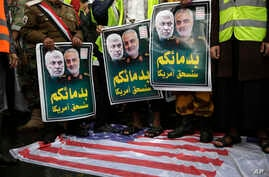 Yemeni Shiite Houthis stand on a representation of an American flag while holding posters of Iraqi militia commander Abu Mahdi…