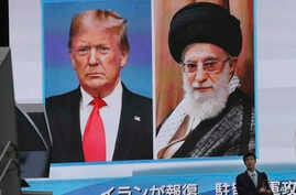 A man walks by a huge screen showing U.S. President Donald Trump, left, and Iranian Supreme Leader Ayatollah Ali Khamenei, in Tokyo, Jan. 8, 2020.