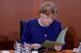 German Chancellor Angela Merkel reads documents after she arrives for the weekly cabinet meeting of the German government at the chancellery in Berlin, Germany, Jan. 8, 2020.