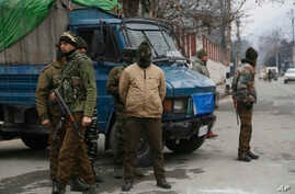 Indian policemen guard as a convoy of New Delhi-based diplomats passes through Srinagar, Indian controlled Kashmir, Jan. 9, 2020.
