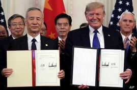 President Donald Trump signs a trade agreement with Chinese Vice Premier Liu He, in the East Room of the White House.