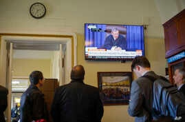 Members of the media in the press gallery watch a television monitor of Supreme Court Chief Justice John Roberts.