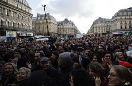 A crowd listens to musicians performing outside the Palais Garnier opera house, Jan. 18, 2020 in Paris.