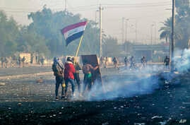 Protesters wave the national flag as security forces fire tear gas during an ongoing protest in central Baghdad, Iraq, Monday,…
