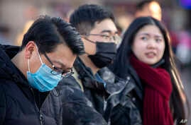 Travelers wear face masks as they walk outside of the Beijing Railway Station in Beijing, Jan. 20, 2020.