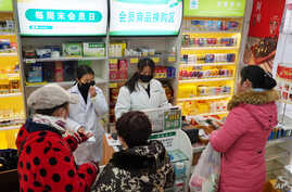 Staff sell masks at a Yifeng Pharmacy in Wuhan, Chin, Jan. 22, 2020.