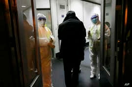 Health Officials in hazmat suits wait at the gate to check body temperatures of passengers arriving from the city of Wuhan.