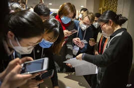 Journalists wearing face masks look at a Chinese government statement before an official press conference.