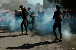 Anti-government protesters run while security forces fire tear gas during clashes in Baghdad, Iraq, Monday, Jan. 27, 2020.