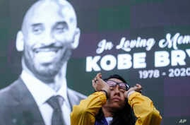 Nicole Mascarenhas, wipes her eyes in front of a screen with the late Kobe Bryant at a memorial for Kobe Bryant near Staples Center, Jan. 27, 2020, in Los Angeles.