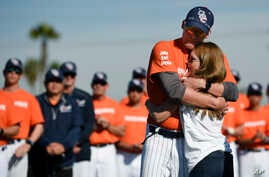 Associate coach Nate Johnson, left, embraces his wife Jonai during a ceremony held for John Altobelli, the late head coach of Orange Coast College baseball, who died in a helicopter crash alongside former NBA basketball player Kobe Bryant in Costa Mesa, California, Jan. 28, 2020.