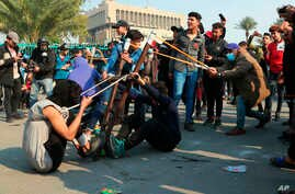 Anti-government protesters use a slingshot to fire a stone at security forces during clashes in Baghdad, Iraq, Jan. 30, 2020.