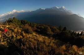 FILE - In this Oct. 24, 2014, file photo, trekkers watch the sun rise over the Annapurna Range, right, in central Nepal