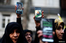 FILE PHOTO: Iranian demonstrators hold up mobile phones showing the picture of the late Iranian Major-General Qassem Soleimani,…