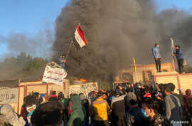 A headquarters building of Popular Mobilization Forces (Hashd al-Shaabi) burns after being torched by demonstrators during…