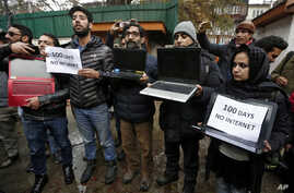 FILE - Kashmiri journalists display laptops and placards during a protest demanding restoration of internet service, in Srinagar, November 12, 2019.